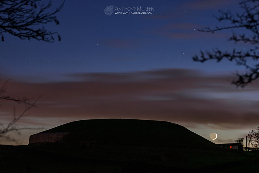 Crescent moon rolls down the mound of Newgrange